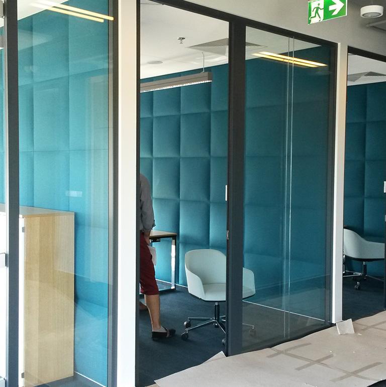 Pokój wyłożony niebieskimi panelami-akustycznymi-z-zamkniętymi szklanymi drzwiami